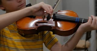 Pre teenage boy playing violin passionately