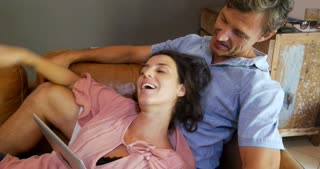 Pregnant loving happy laughing woman and man with a digital tablet having fun spending quality time together