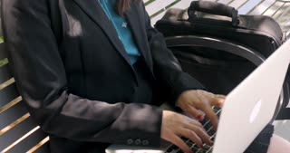 Pretty 30 year old woman working on a laptop computer on a park bench answering her smart phone outside in 4k