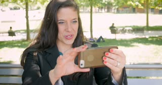 Pretty traveling woman in business suit using smart phone for video conferencing call waiving hello in 4k outside on park bench in public dolly shot