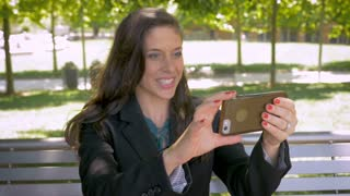 Pretty woman in business suit using smart phone for video conferencing call waiving hello in slow motion outside on park bench in public dolly shot