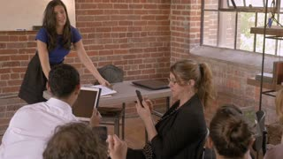 Professional businesswoman unable to get the attention of her audience during presentation as they are all using their digital smart phone and tablet technology in slow motion