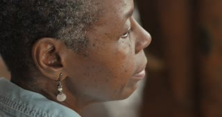 Profile of a beautiful African American elderly woman in her 50s or 60s siting and listening to music waiting - OTS