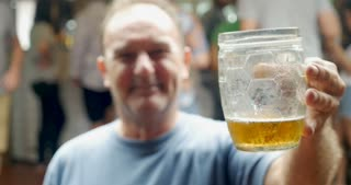 Profile of a man in his 50s or 60s holding a beer mug or glass out to the camera in a bar pub