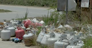 Propane tanks and canisters thrown away in the grass next to a dumpster as a pickup truck drives - dolly shot