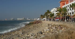 PUERTO VALLARTA, MEXICO - CIRCA MARCH 2018 - Establishing shot of people walking on the Malecon with views of the hotel zone during high tourist season including passengers from cruise ships