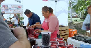 PUERTO VALLARTA, MEXICO - CIRCA MARCH 2018 - Man paying for fresh berries from Mexican vendors at the Olas Altas Saturday farmers' market with a 100 peso bill