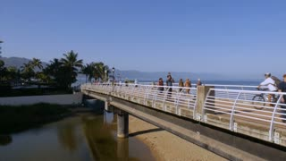 PUERTO VALLARTA, MEXICO - CIRCA MARCH 2018 - Mexican and North American tourists walking across the Rio Cuale Bridge on the Malecon in slow motion