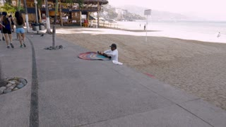 PUERTO VALLARTA, MEXICO - CIRCA MARCH 2018 - Mexican vendor rolling up beach rugs for sale on the Malecon boardwalk