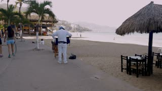 PUERTO VALLARTA, MEXICO - CIRCA MARCH 2018 - Vendor tying his apron getting ready for his day of selling pastries off the Malecon on the beach in slow motion