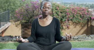Push in of a healthy retired African American senior woman in her 60s sitting quietly meditating