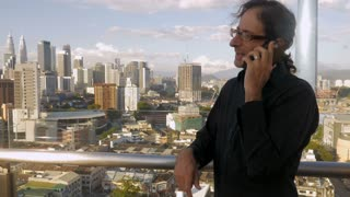 Push in of a man talking on a mobile phone outside overlooking a modern city with large buildings under construction representing economic growth and success in slow motion.