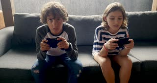 Push in of a young pre teenage boy and girl playing video games together celebrating victory