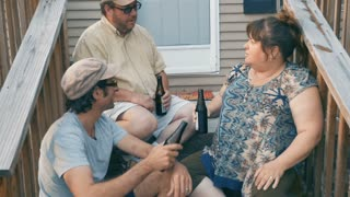 Push in of three friends in their 30s or 40s sitting on porch steps cheering, toasting, and drinking a beer together in slow motion