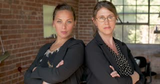 Push in of two attractive serious women with arms crossed looking at camera in a brick building used as a start up new business