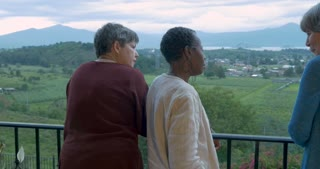 Push in stabilized shot of three female tourists over 60 talking at an overlook vista