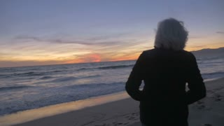 Retired healthy mature active 60s couple hugging and looking at sunset on beach. Traveling baby boomers enjoying ocean on vacation.