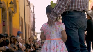 SAN MIGUEL DE ALLENDE, MEXICO - CIRCA MARCH 2016 - Adorable young Mexican girl holding hands and walking with her father during a Semana Santa parade during Easter Holy week