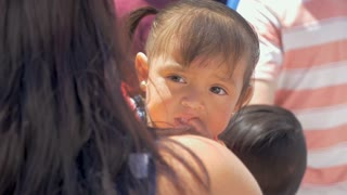 SAN MIGUEL DE ALLENDE, MEXICO - CIRCA MARCH 2016 - Young adorable cute Mexican baby girl with pierced ears sucking on her finger held by her mother in a crowd