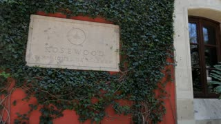SAN MIGUEL DE ALLENDE, MEXICO - CIRCA MAY 2018 - Stone carved Rosewood Hotel sign against a red colorful wall and ivy leaf vines