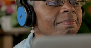 Senior black woman enjoying her music with headphones while looking at a digital display such as a laptop or digital tablet technology