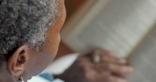 Senior black woman in her 50s or 60s reading a paper book and turning the pages - OTS