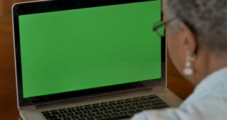 Senior elderly black woman in her 50s or 60s looking at a green screen chroma key computer screen like she is reading information - OTS