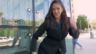Sexy woman in business attire crazy victory dancing her successful lifestyle outside a glass business office building in slow motion