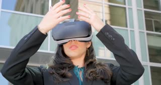 Sexy young female corporate executive in awe holding VR headset experiencing 360 augmented reality technology outside a modern office building in 4k