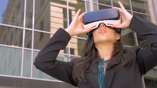 Sexy young female corporate executive in awe holding VR headset experiencing 360 augmented reality technology outside a modern office building in slow motion