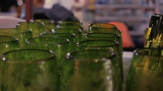 Shelves of etched artisan green glasses in a glass factory