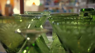 Shelves of etched artisan handmade green wine, cocktail, and shot glasses and water goblets in a glass factory