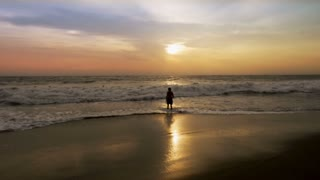 Silhouette of man standing at the edge of the ocean at sunset as a wave approaches in slow motion