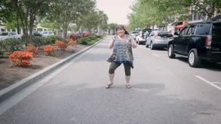 Silly happy smiling woman dancing in street towards camera in urban city environment during day