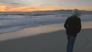 Single mature 60s woman with gray hair walking along beach at sunset. Fit healthy baby boomer exploring upscale coast line at dusk