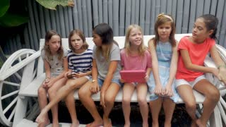 Six young pre teenage girls sitting on a bench both holding digital table and smart phone technology