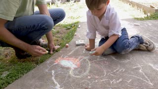 Slow motion of a cute young boy using his left hand to draw with chalk with an adult man outside