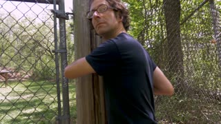 Slow motion of a man in his 30s or 40s trespassing and breaking through a chain link fence and walking into the woods
