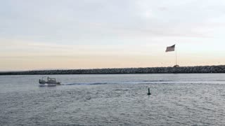 Small motor boat sailing in channel during sunset with American flag waiving along ocean retaining wall with seagulls flying in background