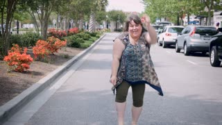 Smiling happy attractive full figured plus sized woman celebrating success achievement dancing in street saying yeah!