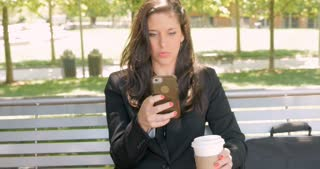 Smiling happy attractive well dressed woman in business suit writing on her smart phone while drinking coffee outside push in 4k