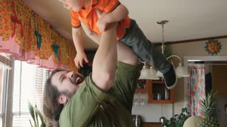 Stay at home dad lifting and playing with his happy smiling baby boy in the air and kissing him in his house