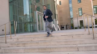 Successful happy handsome corporate male executive businessman dancing down steps celebrating achievement and success in real time outside his office building wide shot