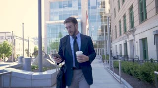 Successful millennial businessman walking away from modern glass office building with smartphone turns it horizontal to view technology video app in slow motion stabilized shot
