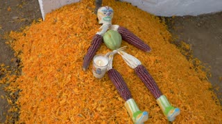 Sugar skull man made with red corn and husks on a grave covered in marigold flower petals during Day of the Dead in Mexico