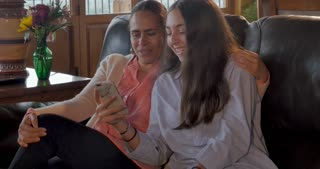 Teenage daughter and Mexican mom looking at a cell phone together laughing while sitting on their living room couch - dolly shot