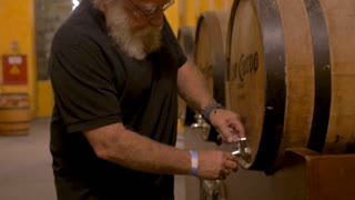 TEQUILA, MEXICO - CIRCA FEB 2017 - Caucasian man with a white beard passing out samples of tequila from a oak cask barrel at the Jose Cuervo distillery factory