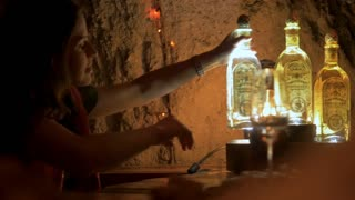 TEQUILA, MEXICO - CIRCA FEB 2017 - Female Mexican tour guide talking about and holding an illuminated bottle of Fortaleza tequila in the tasting cave