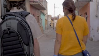 TEQUILA, MEXICO - CIRCA FEB 2017 - Man and woman tourists walking down a colorful small street