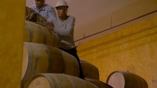 TEQUILA, MEXICO - CIRCA FEB 2017 - Two Mexican plant workers wearing hard hats filling oak barrels with a hose at a factory